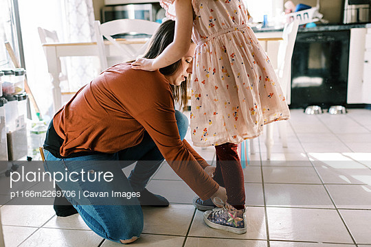 mother helping her daughter put on shoes with laces in kitchen - p1166m2269706 by Cavan Images