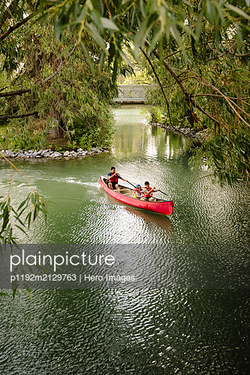 Father canoeing with two sons on lake in park - p1192m2129763 by Hero Images