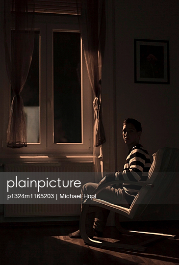 Junger Mann sitzt am Fenster bei Nacht - p1324m1165203 von michaelhopf