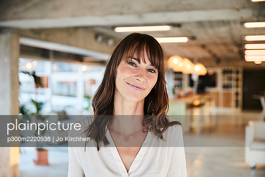 Brown hair mature woman smiling while standing at home - p300m2220938 by Jo Kirchherr
