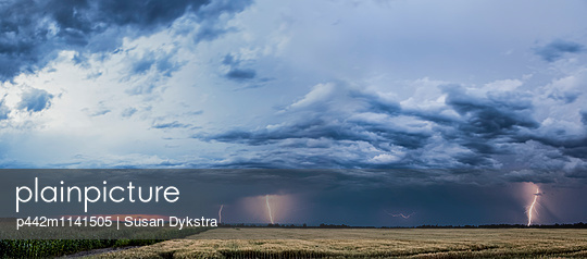 Storm clouds and lightning strikes over a rural landscape; Thunder Bay, Ontario, Canada - p442m1141505 by Susan Dykstra