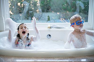 Siblings enjoying in bathtub at home - p1166m1099726f by Cavan Images
