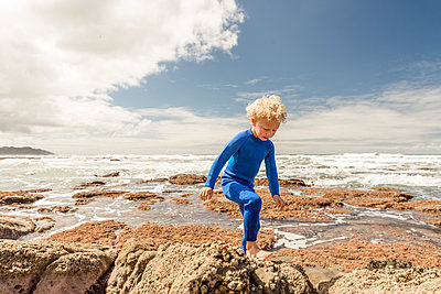 Little boy in blue wetsuit climbing rocks at a beach - p1166m2138183 by Cavan Images