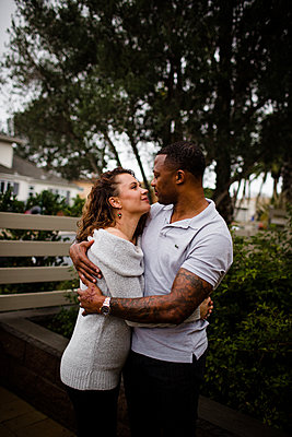 Biracial Couple Embracing & Looking at one Another - p1166m2152204 by Cavan Images