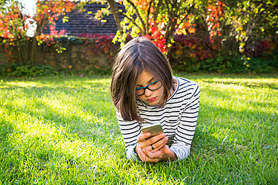 Girl lying on meadow using smartphone - p300m1587959 von Larissa Veronesi