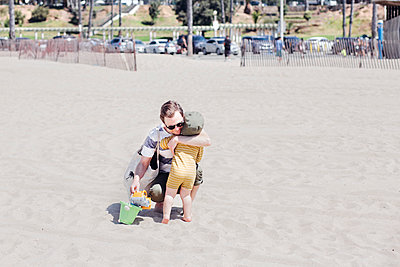 Affectionate father hugging son at beach - p300m2287179 by Ashley Corbin-Teich