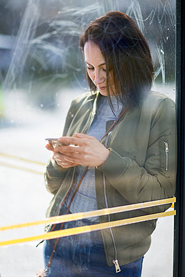 Woman on bus stop using cell phone - p312m1187690 by Susanne Walstrom