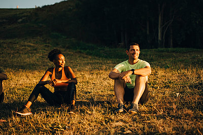 Male and female athletes looking away while sitting on grass during sunset - p426m2270772 by Maskot