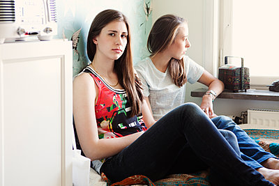 Serious sisters sitting on bed - p555m1409438 by Shestock