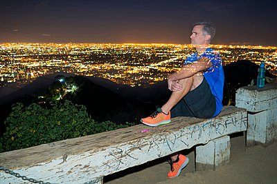 Long exposure of jogger on bench looking away at view, Runyon Canyon, Los Angeles, California, USA - p924m1422782 by Raphye Alexius