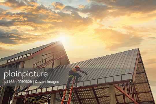 Roofer Construction worker install new roof,Roofing tools - p1166m2292609 by Cavan Images