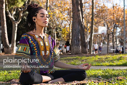 Beautiful young woman meditating while practicing lotus position yoga at park on sunny day - p300m2243312 by NOVELLIMAGE