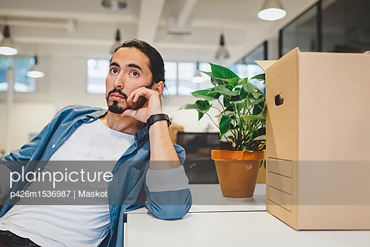 Thoughtful young businessman sitting by cardboard box and potted plant in new office - p426m1536987 by Maskot