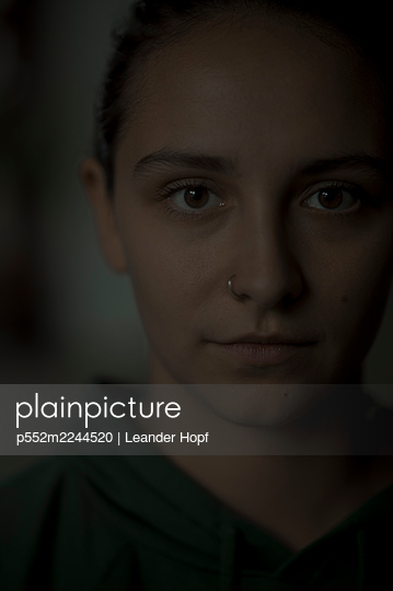 Portrait of young woman with nose piercing - p552m2244520 by Leander Hopf