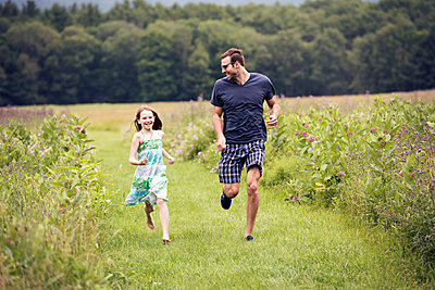 A man and a young child running through a wildflower meadow.  - p1100m1069763f by Mint Images
