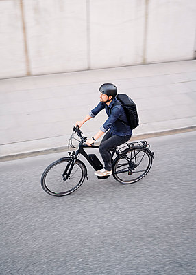 Bicycle courier riding an electric bike - p1124m2053007 by Willing-Holtz
