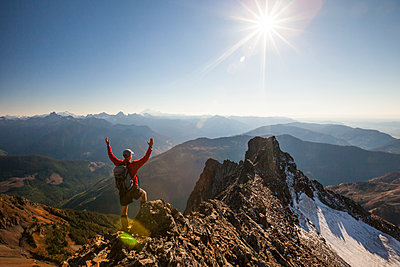 Rear view of male hiker with arms raised standing on rocky mountains during sunny day - p1166m1474180 by Cavan Images
