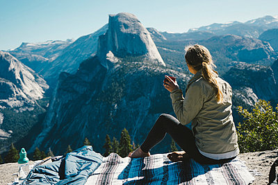 Full length of female hiker having drink while sitting on mountain at Yosemite National Park during sunny day - p1166m2040356 by Cavan Images