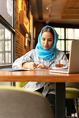 Businesswoman wearing turquoise hijab in a cafe and writing in notebook - p300m2143606 by Eloisa Ramos