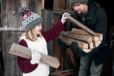 Daughter giving firewood to her father in winter - p300m2160064 by Ekaterina Yakunina