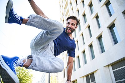 Portrait of happy man jumping in the city - p300m2166906 by Philipp Nemenz
