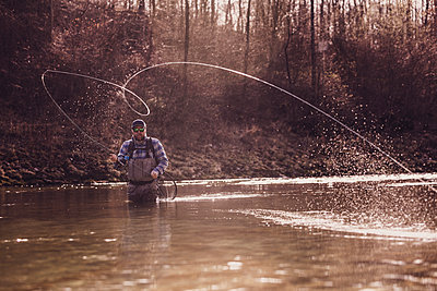 Mid adult man throwing fishing reel in river to catch fish during sunset - p300m2220593 by Studio 27