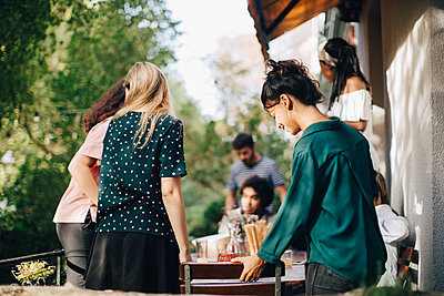 Multi-ethnic male and female friends at table in balcony during party - p426m2046233 by Maskot