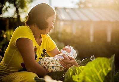 Caucasian mother holding baby girl in garden - p555m1418701 by Aleksander Rubtsov