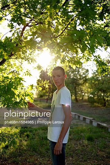 Jugendlicher mit Kurzhaarschnitt unter einem Baum - p1468m1584985 von Philippe Leroux
