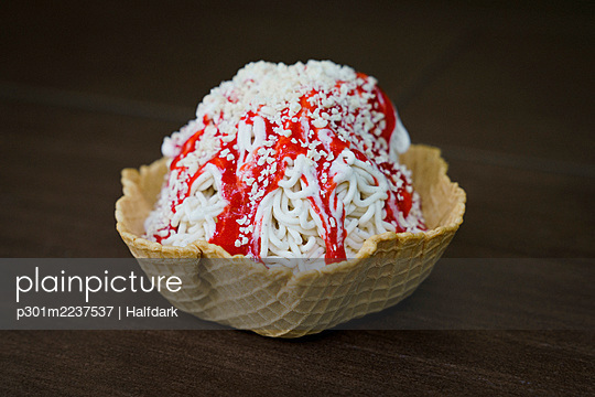 Close up Spaghettieis ice cream sundae with strawberry sauce in waffle cone cup - p301m2237537 by Halfdark