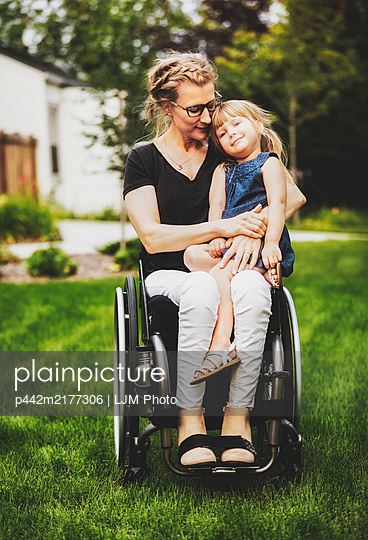A paraplegic mom holding her little girl in her lap while sitting in her wheelchair in her front yard on a warm summer afternoon: Edmonton, Alberta, Canada. - p442m2177306 by LJM Photo