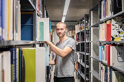 Student am Bücherregal in der Bibliothek - p1284m1452129 von Ritzmann