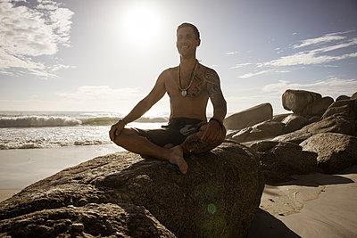 Mann meditiert auf dem Strand im Sonnenschein - p1640m2261016 von Holly & John