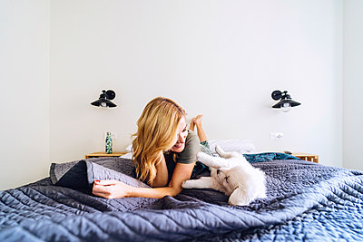 Blond woman playing with puppy on bed against white wall at home - p300m2250494 by Daniel González