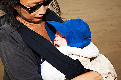 Mother carrying baby son in baby carrier - p429m802437 by Cultura