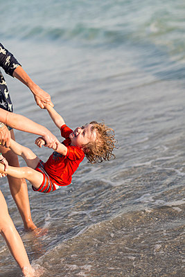 Caucasian family playing on beach - p555m1411375 by Marc Romanelli