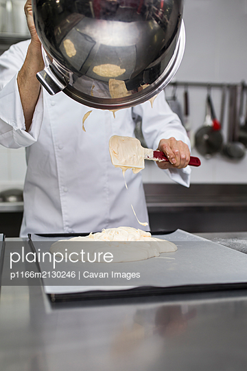 Chef putting dough out of bowl on cooking tray - p1166m2130246 by Cavan Images
