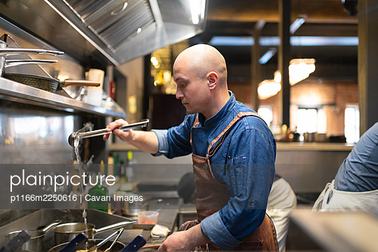 Bald chef pouring water on pan - p1166m2250616 by Cavan Images