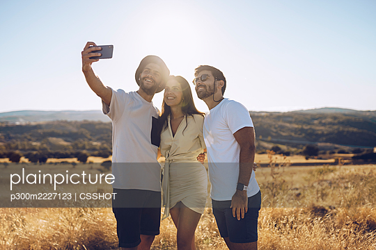 Smiling male and female friends taking selfie through smart phone while standing on field in summer - p300m2227123 by CSSHOT