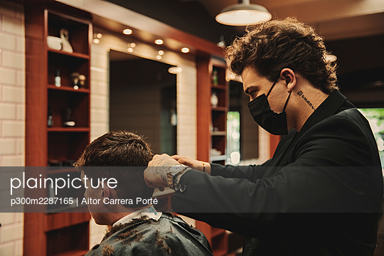 Close-up of a stylish barber with a mask cutting a young guy's hair with a hair clipper in his barbershop - p300m2287165 von Aitor Carrera Porté