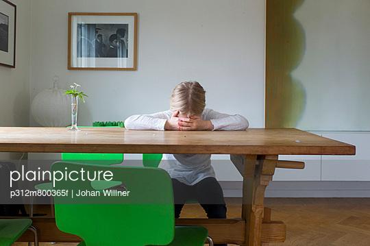 Sad girl sitting at table