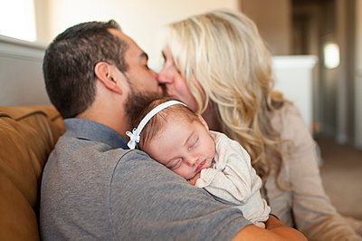 Close up of newborn baby sleeping with parents kissing in background - p1166m2136602 by Cavan Images