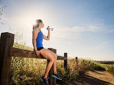 Woman in sportswear drinking from water bottle - p1427m2038332 by Erik Isakson