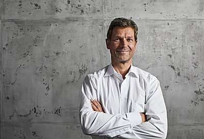 Portrait of smiling mature man in front of concrete wall - p300m1581452 von Philipp Dimitri