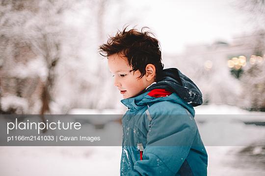 Boy walking in park during winter - p1166m2141033 by Cavan Images