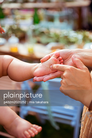 Mutter streichelt Babyfuß - p432m2020252 von mia takahara