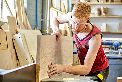 Carpenter holding pencil in mouth while working in workshop - p1166m1489757 by Cavan Images