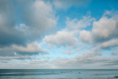 Distant view of people swimming in sea against cloudy sky - p1166m1545863 by Cavan Social