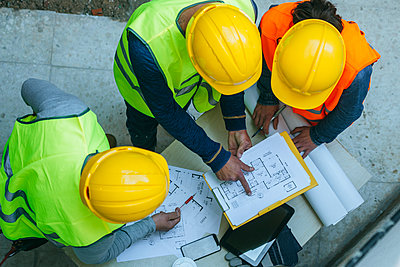 Woman and two men in workwear discussing construction plan - p300m1356296 by Kiko Jimenez
