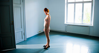Woman in empty room - p4130466 by Tuomas Marttila